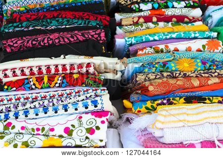 Folded colorful authentic Mexican women's shirts on sale