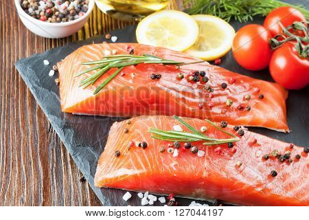 Raw salmon fillet and ingredients for cooking on a slate board and  brown wooden background.