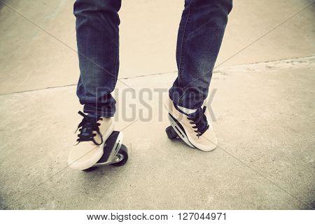 young skateboarder legs practice freeline at skatepark