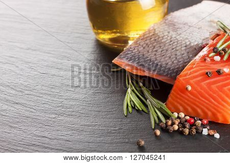 Raw salmon fillet and spices on a dark  slate background