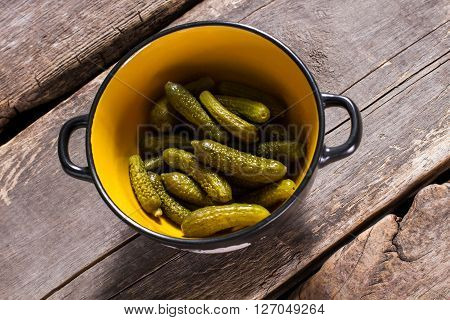 Pickles in bowl with handles. Bowl of pickles on table. Recipe of sour marinated pickles. Small and crispy vegetable.