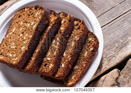 Slices of bread on plate. Brown bread on wooden background. Work of skillful baker. Simple snack that gives energy.