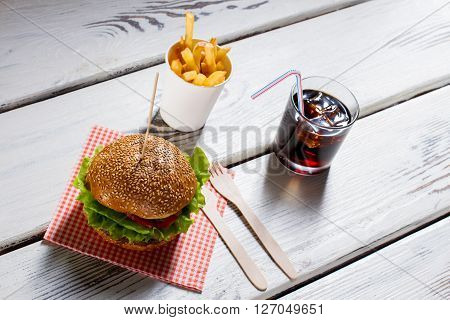 Burger and fries with cola. Burger with cutlery and drink. Hamburger menu on white table. Tasty high-calorie food.