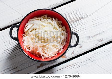 Sauerkraut in a bowl. Bicolor bowl filled with sauerkraut. White table with fresh sauerkraut. Product that has sour taste.