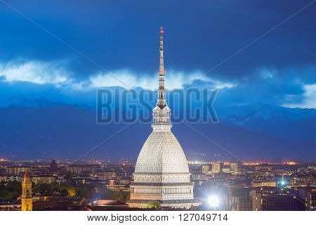 Cityscape of Torino (Turin Italy) at dusk with details of the Mole Antonelliana towering on the city and glowing in the night. Wind storm over the Alps in the background.