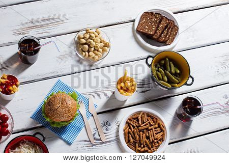 Burger with cola and bread. Crackers, burger and cola glass. Tasty meal on bistro table. It's lunch time.