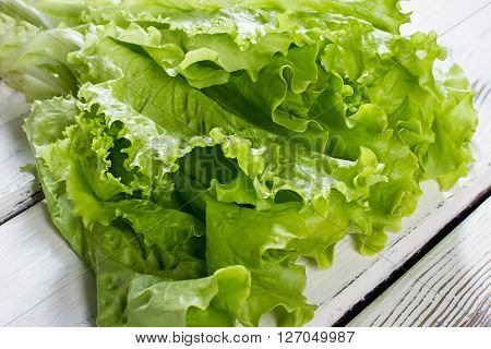 Green lettuce leaves. Lettuce leaves on wooden background. Fresh lettuce on kitchen table. Healthy organic food.