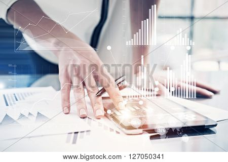 Picture female hand touching modern tablet.Investment manager working new private banking project office.Using electronic device. Graphic icons, worldwide stock exchanges interface on screen.