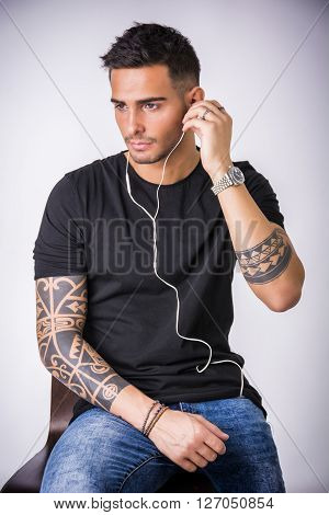Attractive young man with earphones listening to music, on light background
