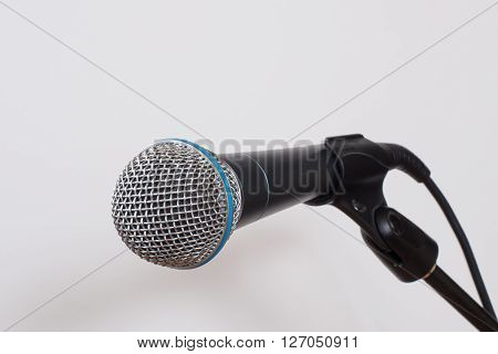 Clean shot of a microphone (mic) against a white background ready to be grabbed and used.