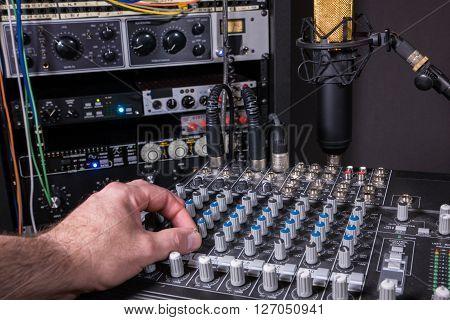 Engineer adjusting level settings on mixing console in recording studio setting.