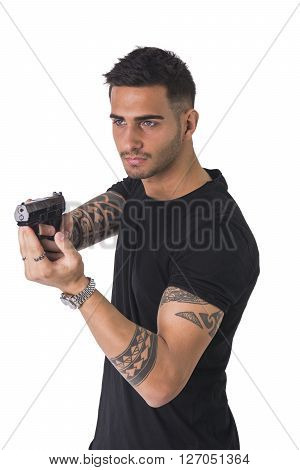 Young handsome man pointing gun, wearing black t-shirt, isolated on white background