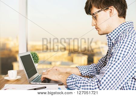Sideview of caucasian male typing on laptop.