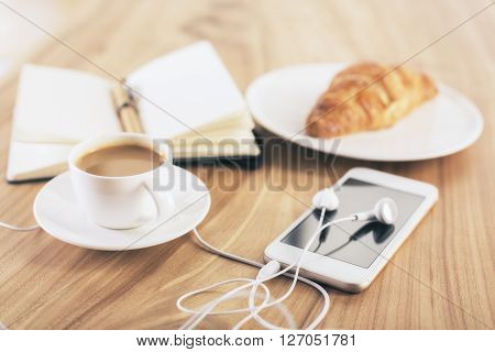 Closeup of wooden desktop with coffee croissant phone with headphones and notepad