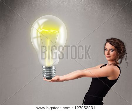 Beautiful young lady holding realistic 3d light bulb