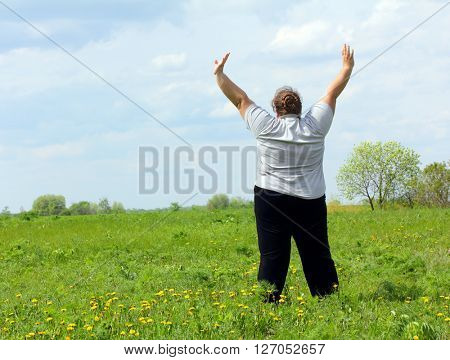 overweight woman with hands up exercising on green meadow