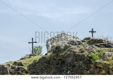 Medieval stone orthodox chapel exterior and christian cross on mountain hill