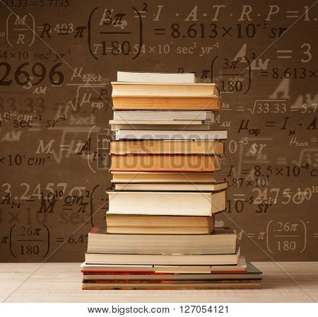 Books on vintage background with math formulas flying out