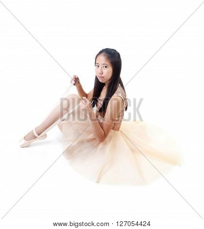 Young Asian Ballerina Tying Her Ballet Pointe Shoes