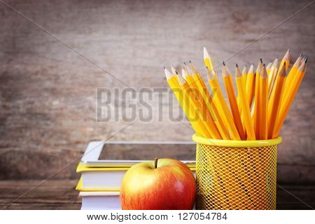 Set of pencils in metal holder, books, tablet and apple on wooden background
