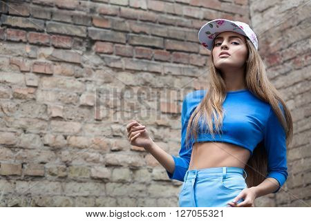 Fashion Portrait Of Stylish Hipster Girl, Wearing Bright Swag Hat, Blue Pants And Top Blouse. Posing