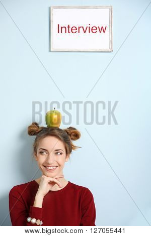 Portrait of young woman with apple on head waiting for interview against blue wall background