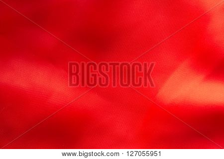 Shiny red silky fabric folds background texture
