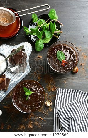 Glass cups of chocolate dessert with fresh mint on black wooden table
