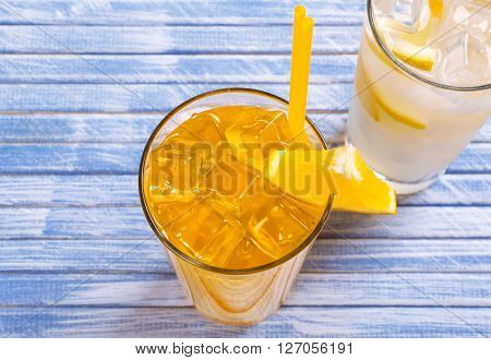 Glass of orange juice with ice on wooden background