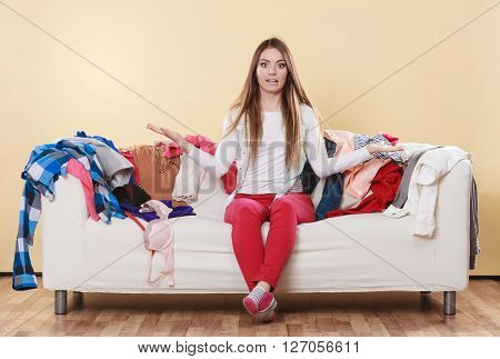 Helpless woman sitting on sofa couch in messy living room shrugging. Young girl surrounded by many stack of clothes. Disorder and mess at home.