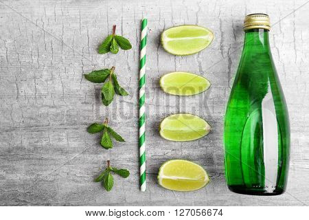 Fresh cocktail preparation: soda bottle, ice cubes, slices of lime, straw on grey table background, top view
