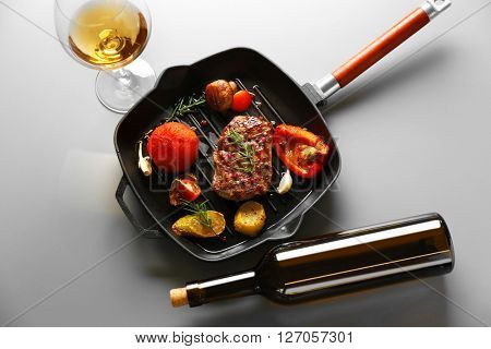 Delicious grilled steak on pan with white wine