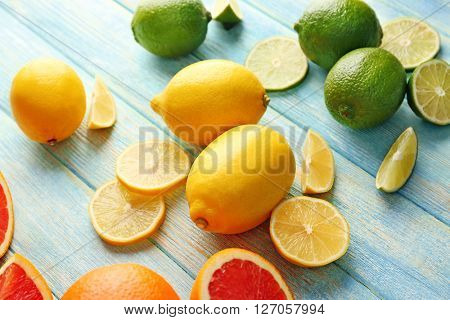 Juicy composition of citrus fruits on wooden background, close up