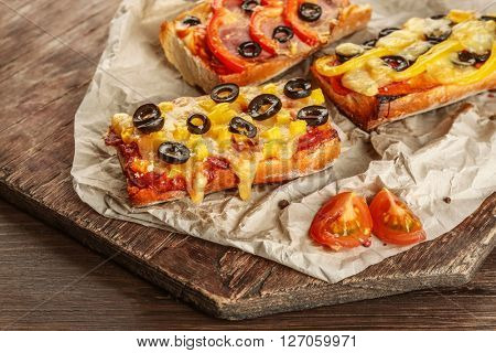 Hot pizza baguettes with paprika, olives and ham on wooden table