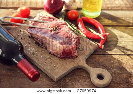 Raw pork steak with meat fork and bottle of red wine on wooden background
