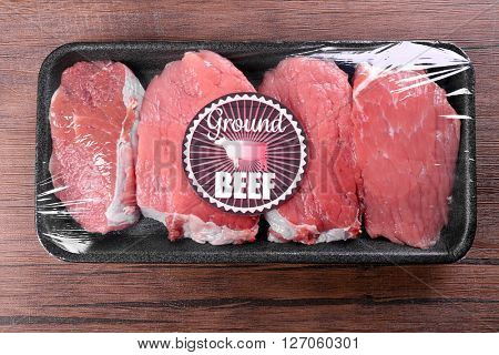 Packed pieces of beef meat on wooden background