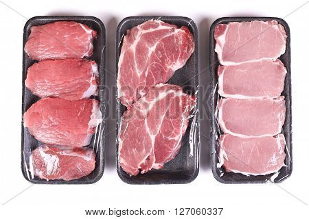 Packed pieces of pork and beef meat, isolated on white
