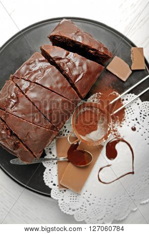 Chocolate sliced cake with icing and cocoa powder on baking dish over white table