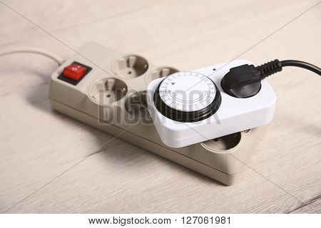 Overloaded power board on wooden floor background