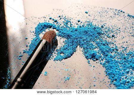 Makeup brush with eye shadow on dark background