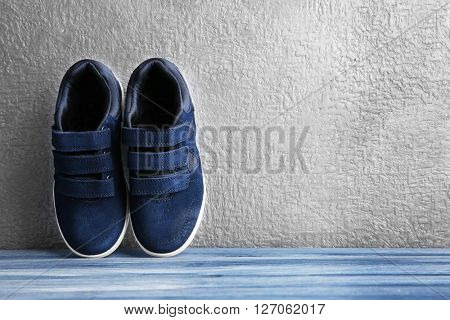 Black sneakers for kid on grey textured background