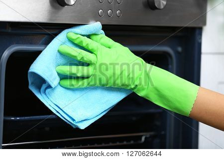 Woman hand in protective glove cleaning oven with rag