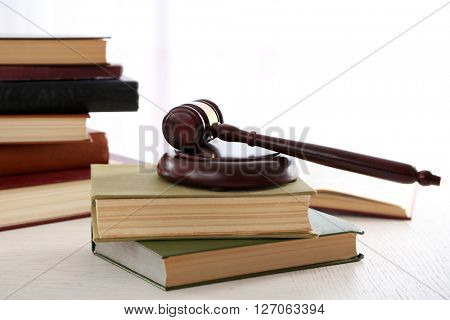 Gavel with books on light blurred background