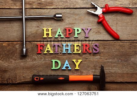 Happy Father's Day inscription with work tools on wooden background. Greetings and presents