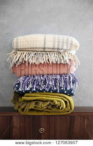 Stack of warm plaids on wooden commode over grey wall background