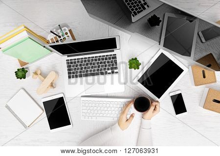 Concept of using electronics. Businesswoman works at office. Computer, laptop, tablet, cup of coffee and other things on the table. Top view