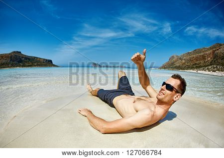 man is sunbathing on the sand on the beach. Male partially in water