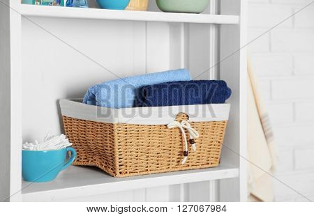 Bathroom set with towels, basket and sponges on a shelf in light interior