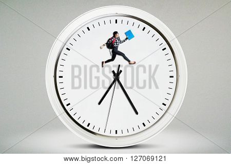 Female high school student carrying bag and jumping on a big clock. Concept of Back to School