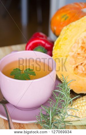 Squash soup and organic pumpkin fresh vegetables: corn red peppers scallion and ginger over a wood table on natural environment. ** Note: Shallow depth of field